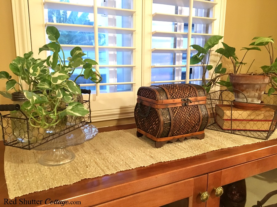 A new approach to styling window countertops includes a couple of plants and a bamboo chest. www.redshuttercottage.com