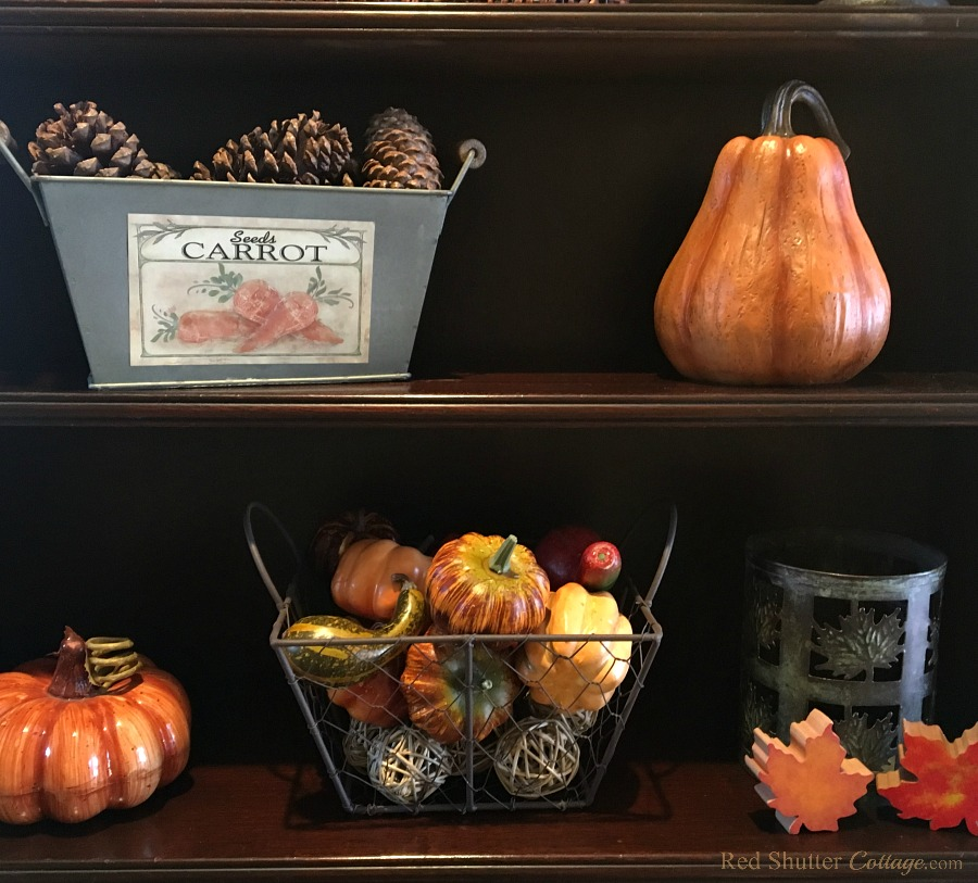 My Grandmother's mahoagany display case is showing harest fruits, pumpkins, pine cone cones and leaves as part of my 2018 Fall Living Room Tour. www.redshuttercottage.com