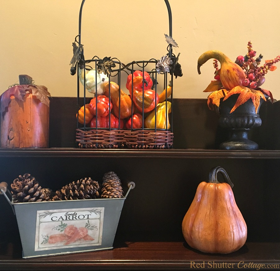 For my 2018 Fall Living Room tour, I filled this wine basket with harvest fruits. This is the top shelf of my Grandmother's display case. www.redshuttercottage.com