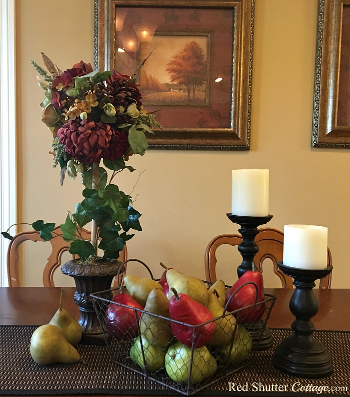 These pears are grouped together in a basket, flanked by candles and topiary showing how easy it is to decorate using alternative fall colors.