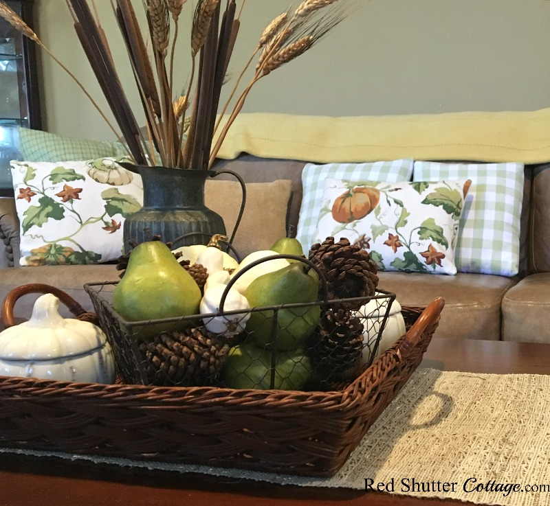 The coffee table holds a basket full of pinecones and pears as part of the Fall 2018 Fall Living Room tour. www.redshuttercottage.com