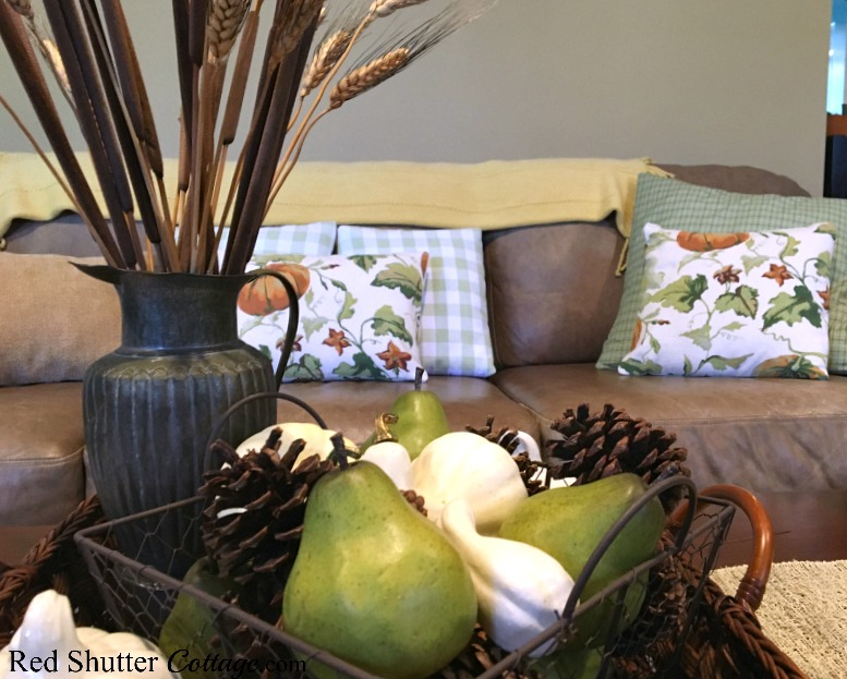 The coffee table is decorated with a large flat basket, a smaller chicken-wire basket, and a pewter pitcher, all part of my 2018 Fall Home Tour. www.redshuttercottage.com
