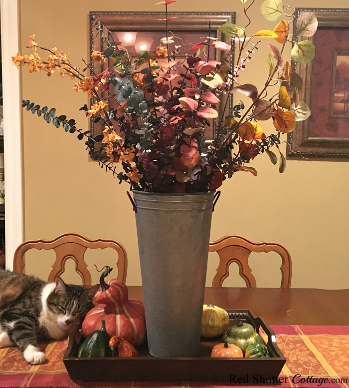 A galvanized metal pail holds a combination of fall leaves and foliage as part of the 2018 Fall Living Room. www.redshuttercottage.com