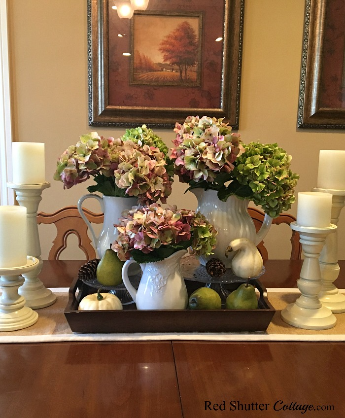 This table-top display of late-summer hydrangeas, pine cones and pears shows how to decorate using alternative fall colors.