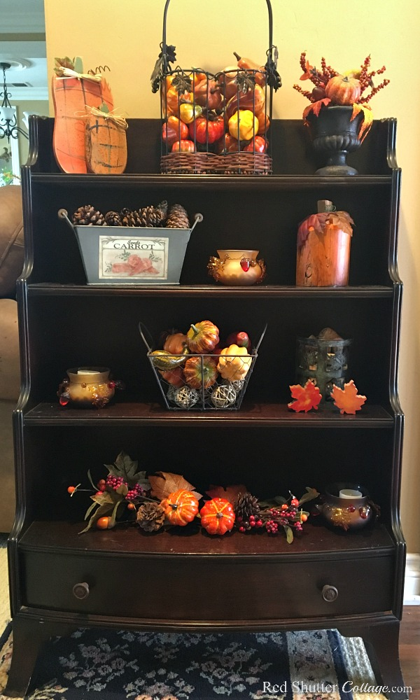 My grandmother's mahogany curio shelf case in our entry decorated with fall elements as part of my 2018 Fall Living Room Tour. www.redshuttercottage.com
