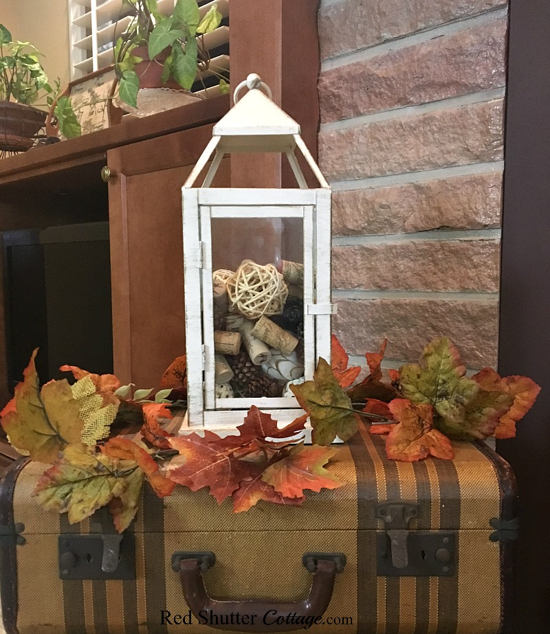 A lantern filled with pine cones, wine corks and twine balls sits on top of a pair of suitcases in the 2018 Fall Living Room. www.redshuttercottage.com