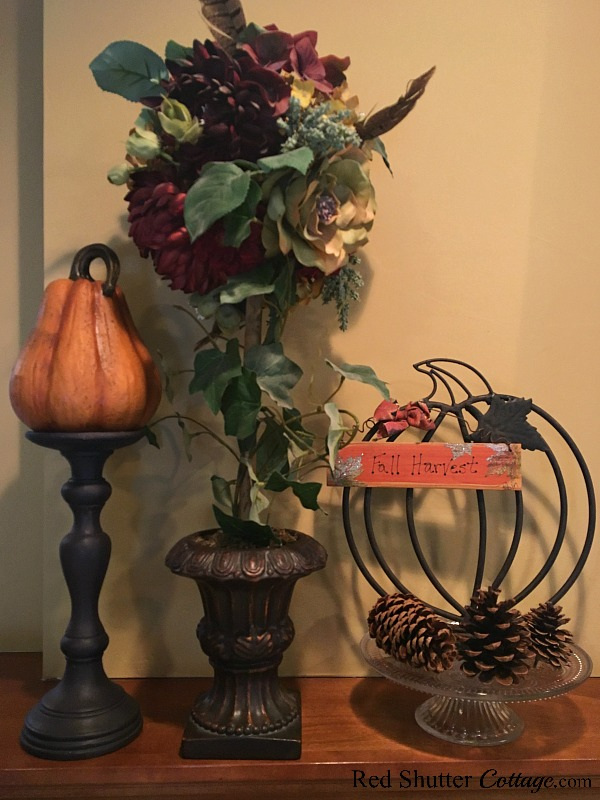 This display on the left hand side of the 2018 Living Room mantel includes a pumpkin on a candleholder, a fall topiary, and a wrought iron pumpkin surrounded by pine cones. www.redshuttercottage.com