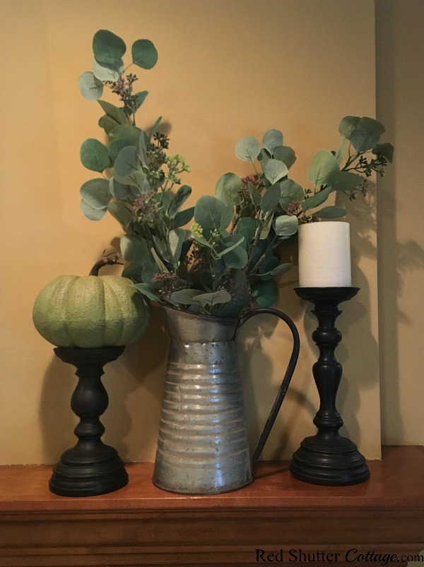 On the right hand side of the 2018 Fall Living Room mantel is a pumpkin sitting on a candleholder, and a bouquet of eucalyptus leaves in a galvanized metal pitcher. www.redshuttercottage.com