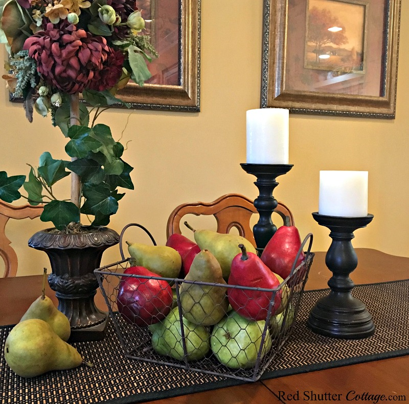 This close-up view of colorful pears grouped with a topiary is part of how to decorate using alternative fall colors. www.redshuttercottage.com