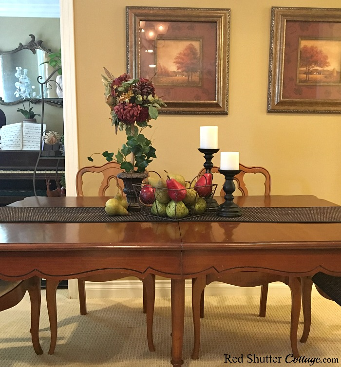 Staged on a dining table is this collection of pears, a topiary and candles showing how to decorate using alternative fall colors. www.redshuttercottage.com