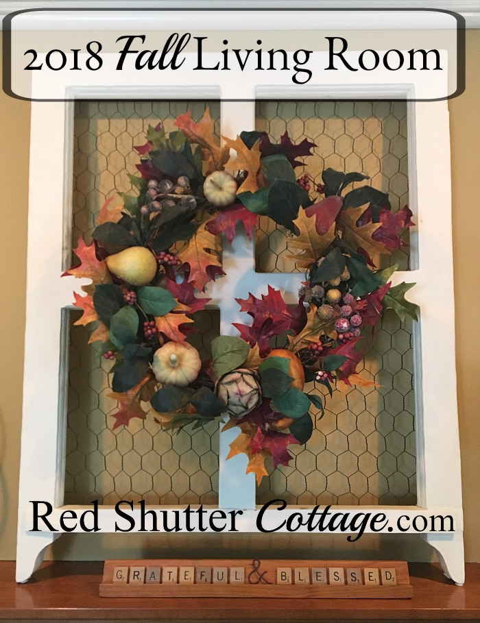 This window frame, complete with chicken wire, is displaying a colorful fall wreath, as part of the 2018 Fall Living Room. www.redshuttercottage.com