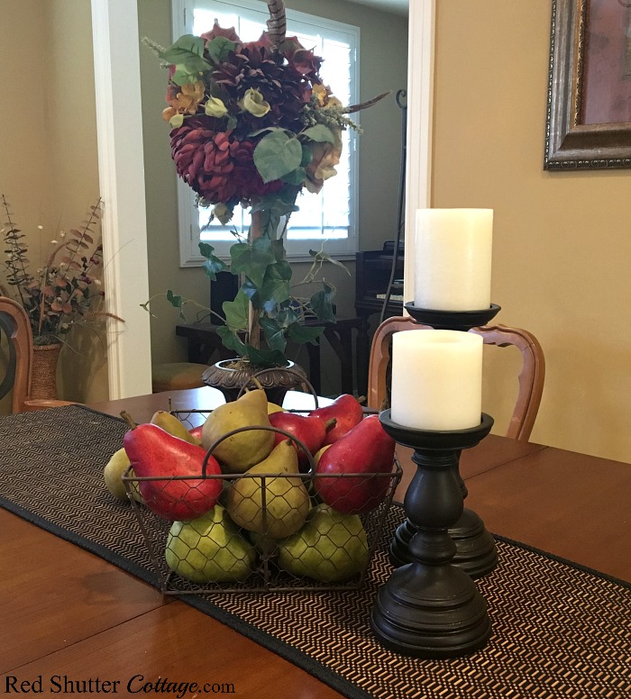 Placed on a runner is a basket of pears and a topiary that are part of how to decorate using alternative fall colors. www.redshuttercottage.com