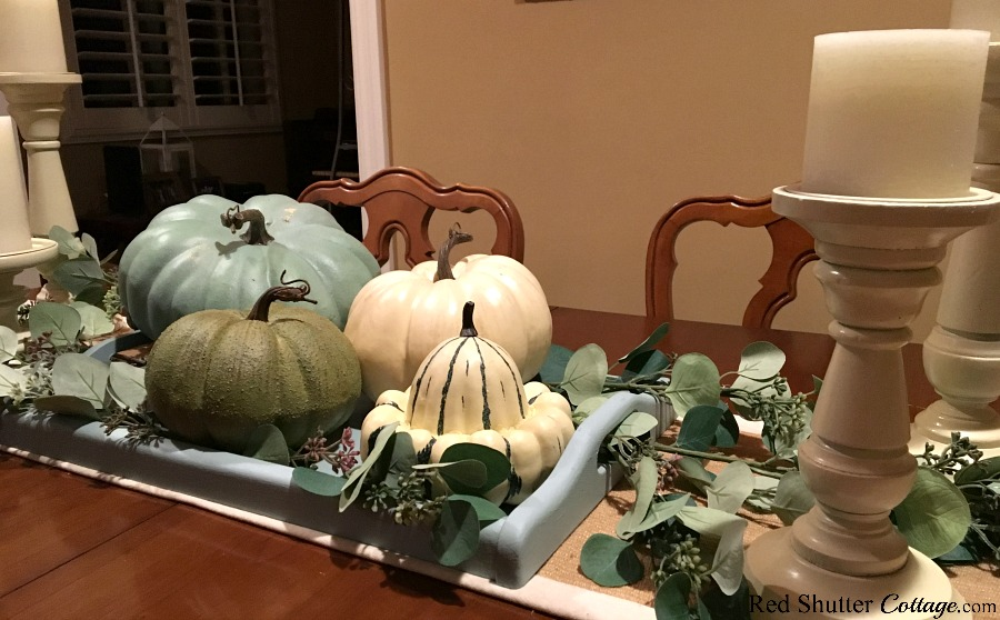 This view of neutral pumpkin nestled in with eucalyptus leaves and candles is part of how to decorate with alternative fall colors. www.redshuttercottage.com