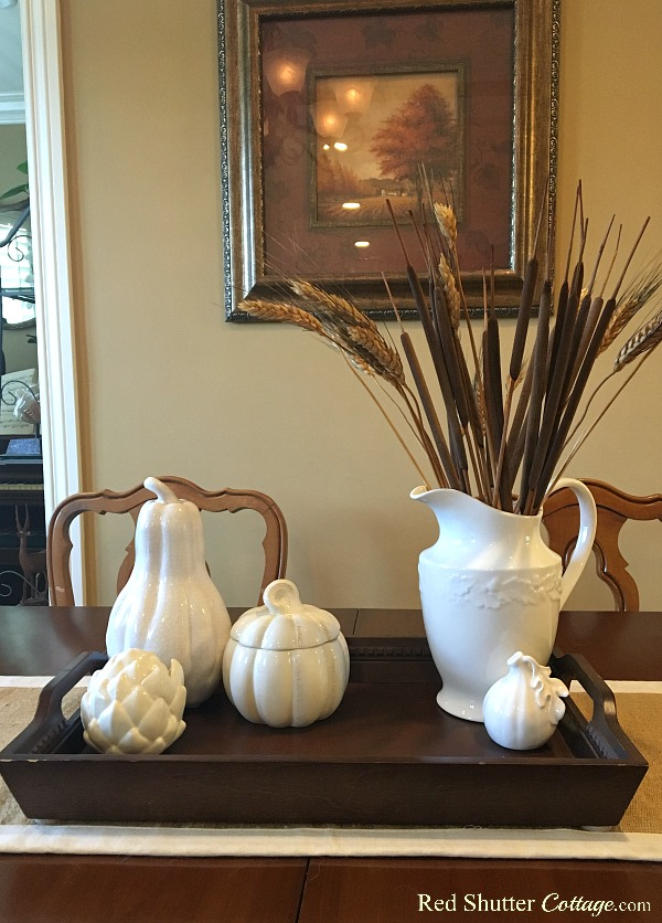 This arrangement of white ceramic ware and a white sheaf comes from how to decorate using alternative fall colors. www.redshuttercottage.com