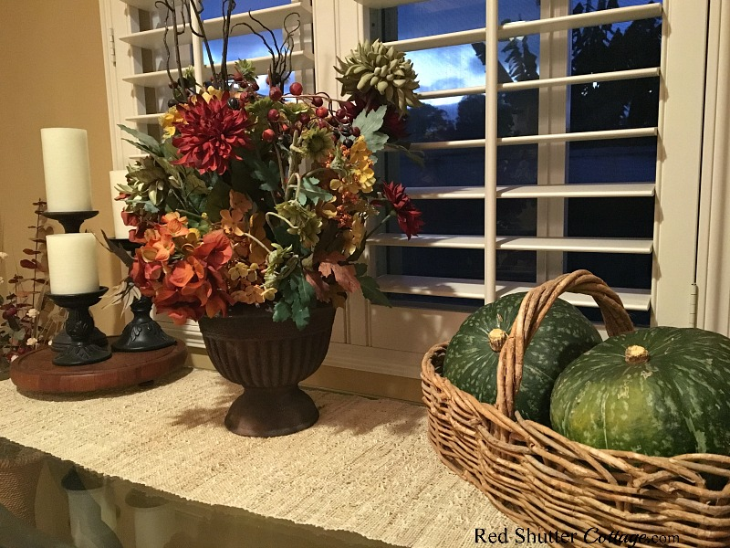 A trio of candles on a wooden tray, a fall floral display, and two kabocha squash tucked into a rustic basket create a warm harvest feel as part of the 2018 Fall Living Room. www.redshuttercottage.com