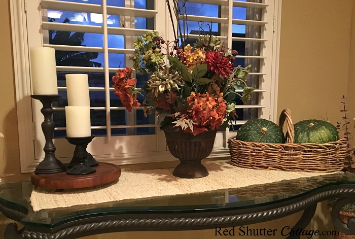 The side table in our dining area is holding a fall bouquet and a pair of kabocha squash. www.redshuttercottage.com