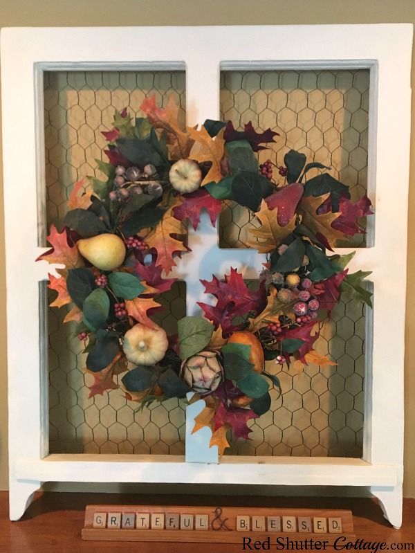 A fall fruit wreath is attached to a window frame and placed on the mantel as part of the 2018 Fall Living Room. www.redshuttercottage.com