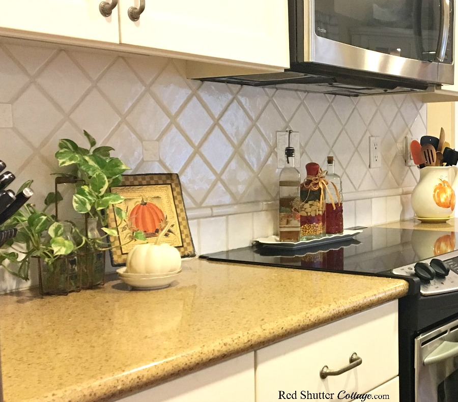 From a different angle, the countertop with pumpkin and plaque, and my pumpkin pitcher holding wooden spoons and spatulas, all included in Fall in the Kitchen 2018. www.redshuttercottage.com