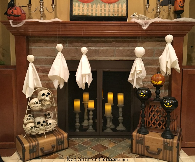 A hearth view including skulls, jack-o'-lanterns and ghosts for a Fun Halloween Mantel. www.redshuttercottage.com