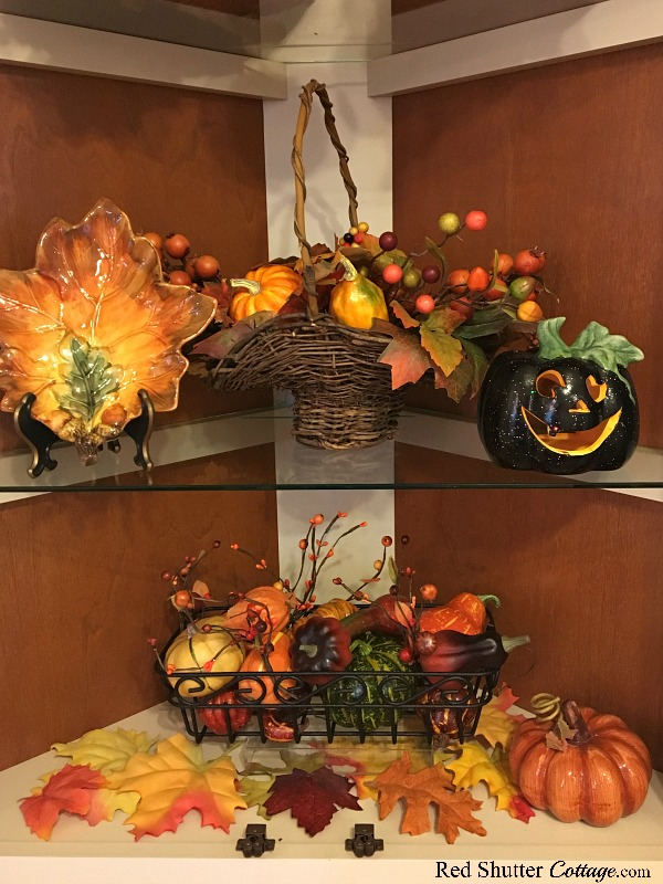 The bottom two shelves in our Fall in the Kitchen 2018 hutch include leaf plates, pumpkins and baskets of fall fruit. www.redshuttercottage.com