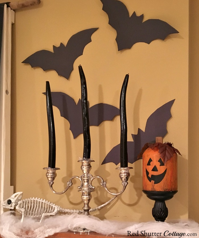 The right side view of a Fun Halloween Mantel includes bats, candles and a dinosaur skeleton. www.redshuttercottage.com
