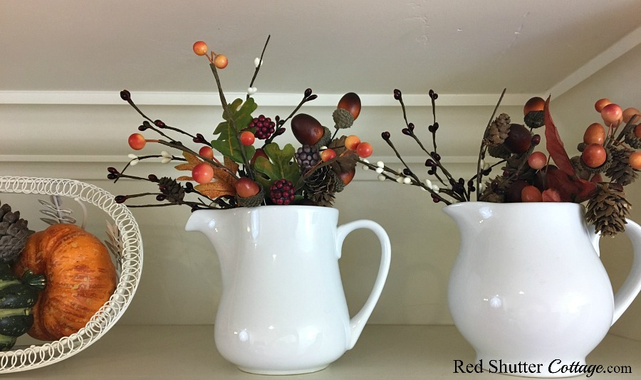 White pitchers filled with berries and pine cones are part of the Fall in the Kitchen 2018. ww.redshuttercottage.com