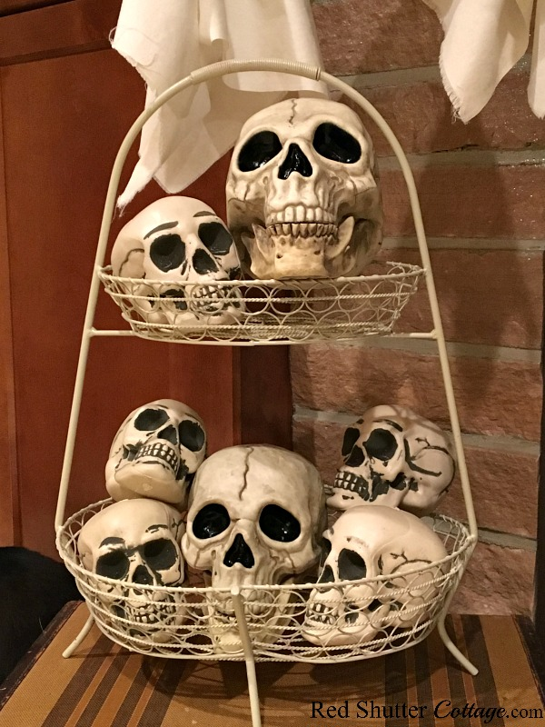 A basket of skulls decorate the hearth of a Fun Halloween Mantel. www.redshuttercottage.com
