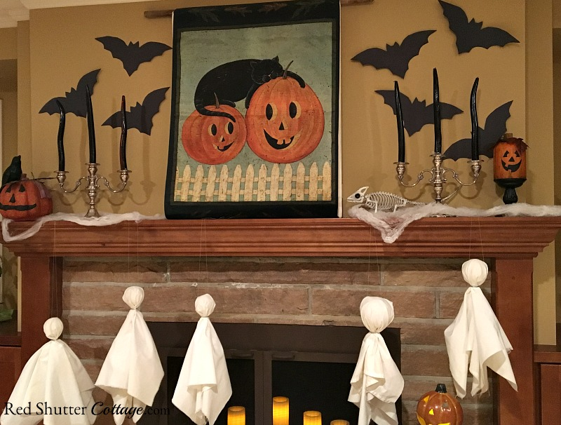 A banner showing a black cat and two jack-o'-lanterns are the focus of a Fun Halloween Mantel. www.redshuttercottage.com