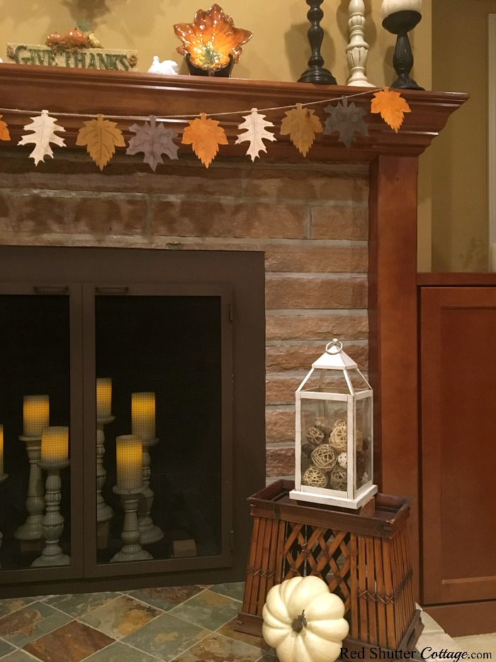 A lantern filled with willow balls and pine cones is part of 2018 Thanksgiving Mantel. www.redshuttercottage.com