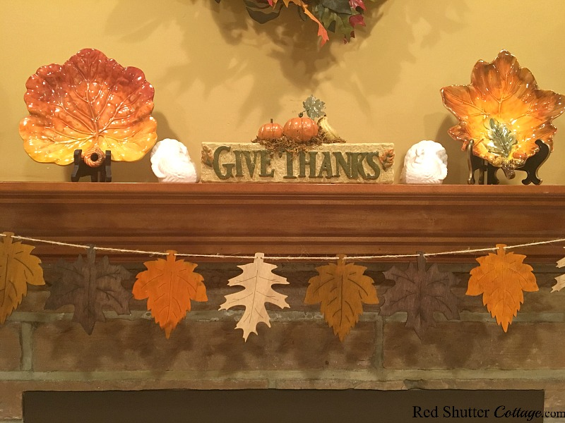 In the center of the 2018 Thanksgiving Mantel are a pair of turkeys and ceramic fall leaves. www.redshuttercottage.com