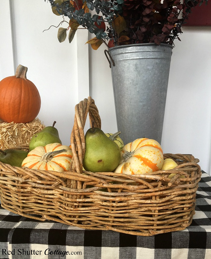 A basket full of gourds and pears are part of A Festive Fall on the Front Porch 2018. www.redshuttercottage.com
