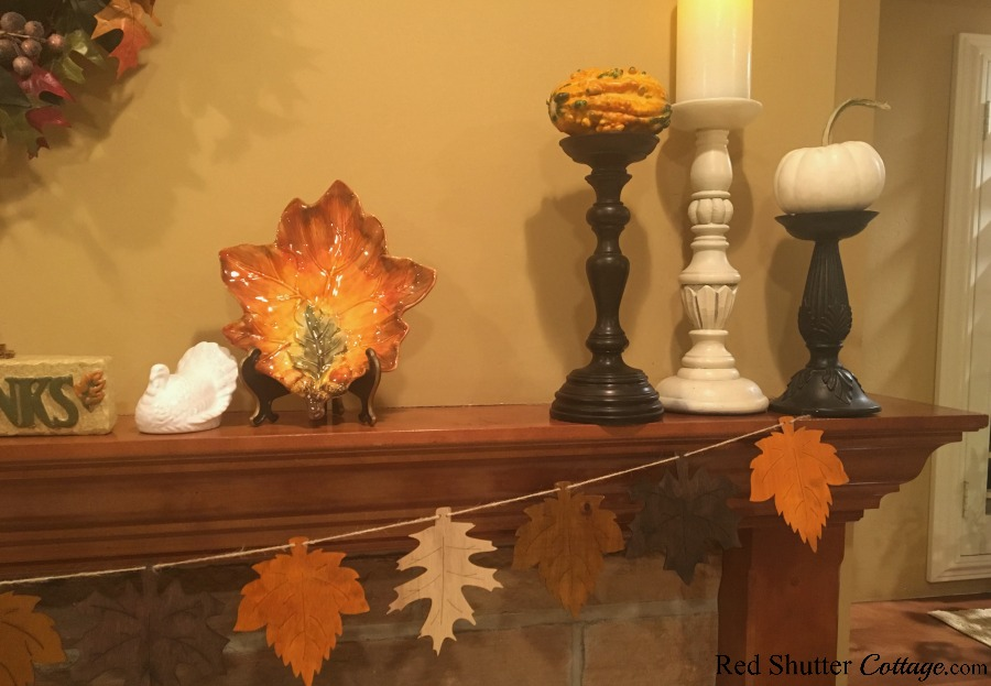 The right hand side of A Thanksgiving Mantel includes gourds and pumpkins on candleholders. www.redshuttercottage.com