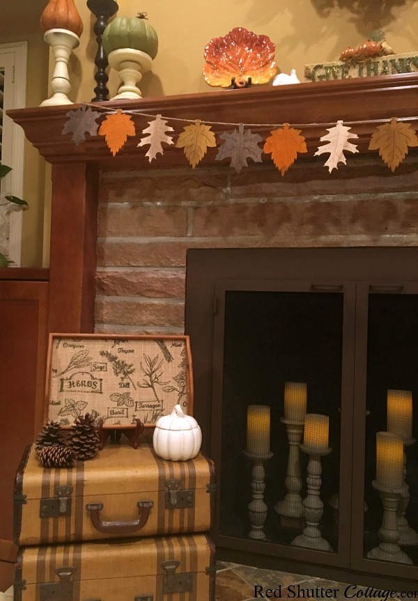 A banner of fall leaves over stacked suitcases is part of the 2018 Thanksgiving Mantel. www.redshuttercottage.com