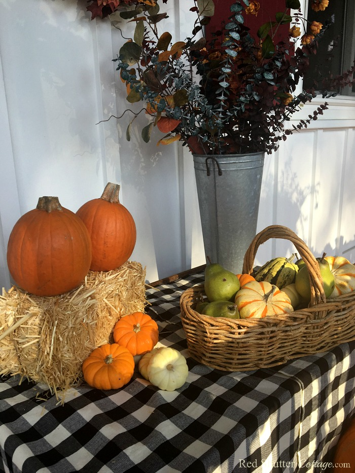 A bale of hay and a buffalo check tablecloth make A Festive Fall on the Front Porch more colorful. www.redshuttercottage.com