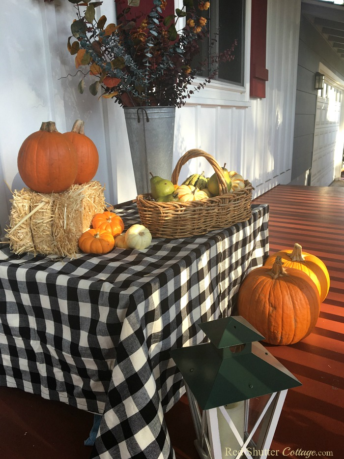 A lantern and some pumpkins in early morning sunshine as part of A Festive Fall on the Front Porch. www.redshuttercottage.com
