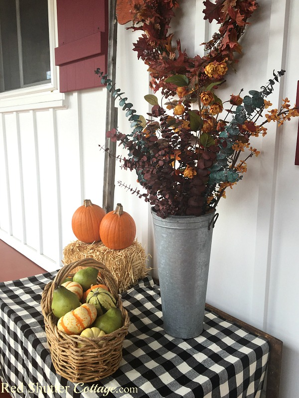 A grouping of pumpkins and fall foliage make up A Festive Fall on the Front Porch. www.redshuttercottage.com