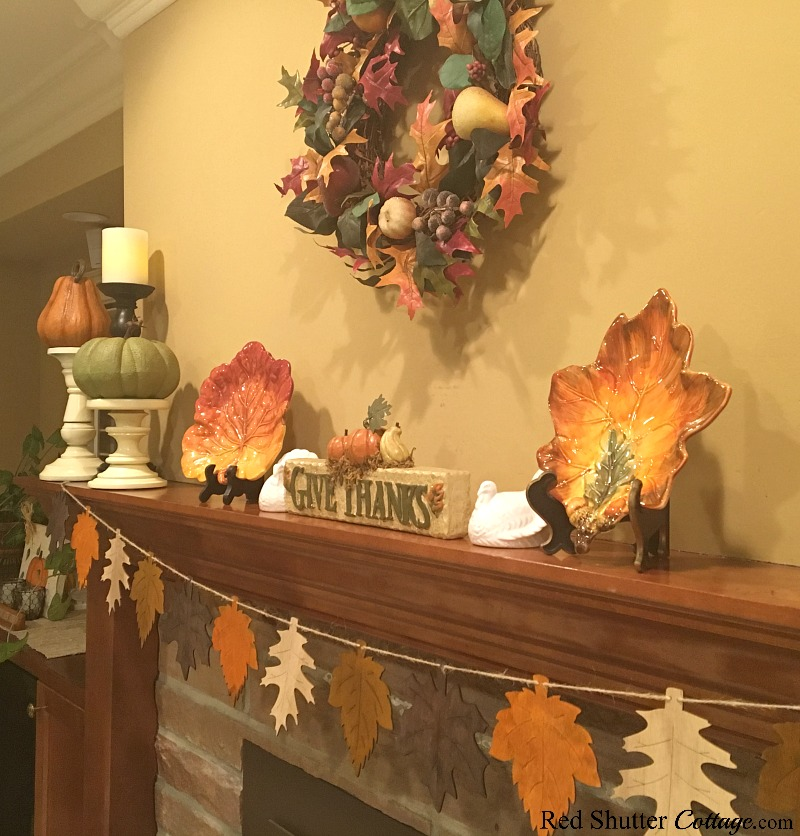 A side view of the 2018 Thanksgiving Mantel includes a wreath, a banner of leaves and a Give Thanks sign. www.redshuttercottage.com