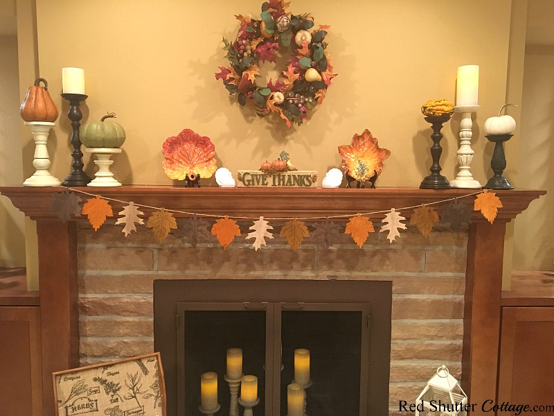 A Thanksgiving mantel with candles and leaves. www.redshuttercottage.com