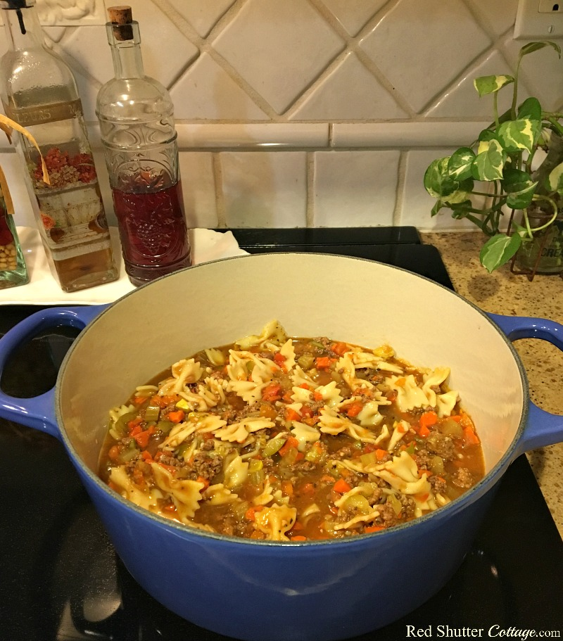 A pot of Beef ~n~ Bowtie soup on the stove filled with delicious vegetables and bullion. www.redshuttercottage.com
