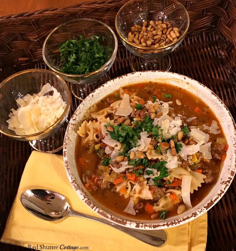 This hearty and flavorful Beef ~n~ Bowtie soup ready to be served, complete with shredded parmesan cheese, parsley and toasted pine nuts. www.redshuttercottage.com