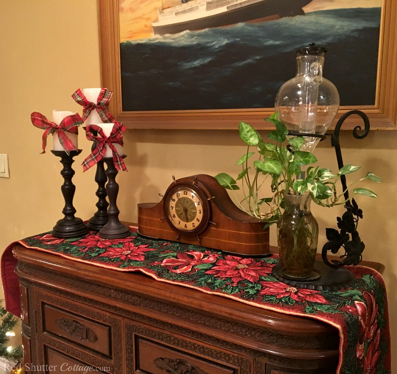 Candles tied with plaid bows on a poinsettia runner are part of the 2018 Christmas Living Room. www.redshuttercottage.com