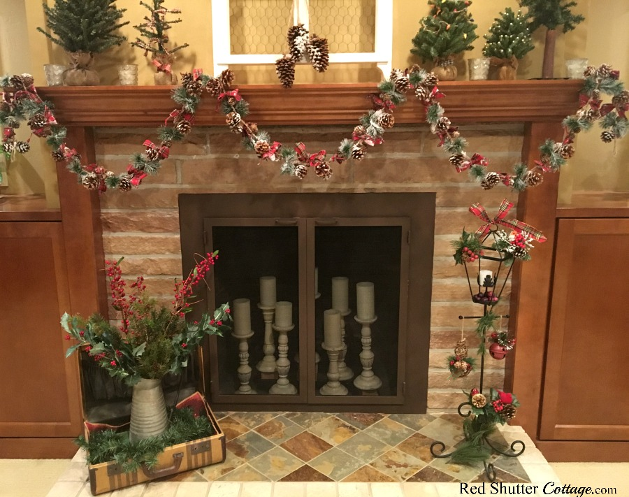 The fireplace and hearth with Christmas plaids, pine cones and greenery, as part of the 2018 Christmas Living Room. www.redshuttercottage.com