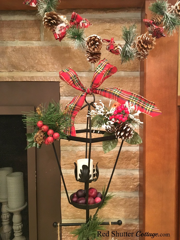 Topped off with a red plaid bow, this black wrought iron lamp post is part of the 2018 Christmas Living Room. www.redshuttercottage.com