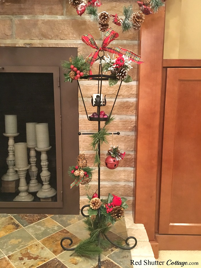 This wrought iron lamppost has been newly revitalized, and is decorated with pine cones, greenery and berries - all part of the 2018 Christmas Living Room. www.redshuttercottage.com