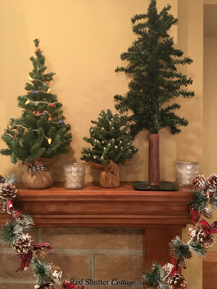 These trees are part of the mantel for 2018 Christmas Living Room. The tree on the far left with the wooden lights came from Indiana. www.redshuttercottage.com