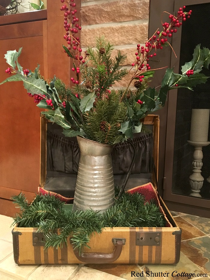 Tucked into a suitcase, surrounded by greens, this galvanized pitcher is part of the 2018 Christmas Living Room. www.redshuttercottage.com