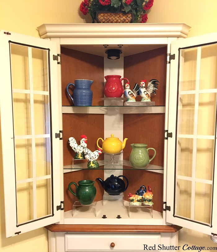 The roosters and pitchers styled in the kitchen hutch, as part of 3 Tips for Styling a Kitchen Hutch and Plate Shelf. www.redshuttercottage.com