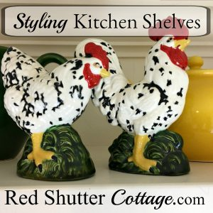 A rooster and hen from a thrift shop are included on the plate shelf, along with other roosters, hens, tea pots and pitchers. All part of 3 Tips for Styling a Kitchen Hutch and Plate Shelf. www.redshuttercottage.com