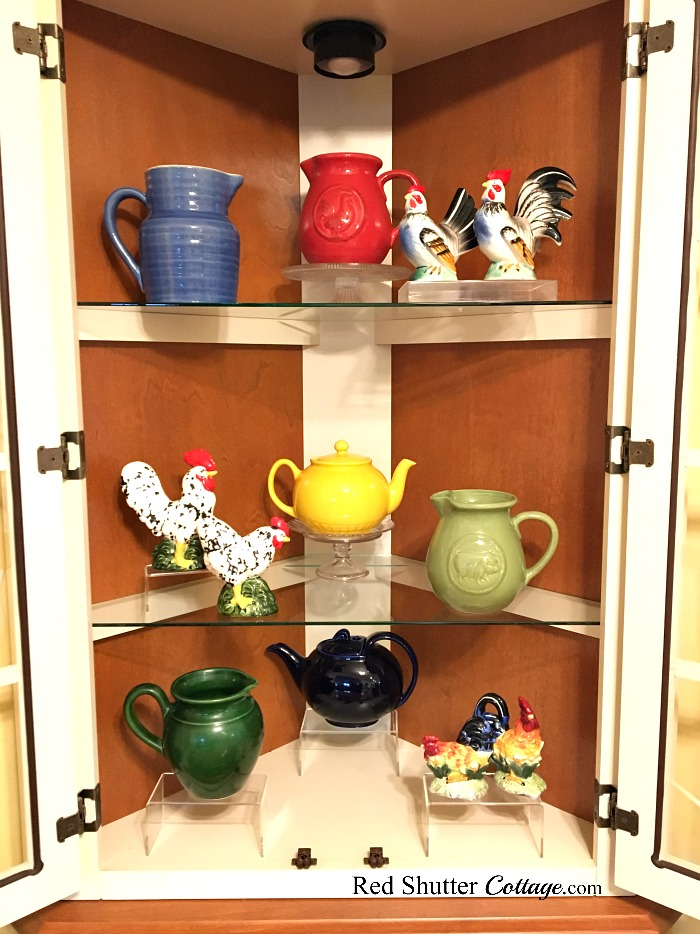A full view of the inside of the hutch filled with colored pitchers and rooster, part of 3 Tips for Styling a Kitchen Hutch and Plate Shelf. www.redshuttercottage.com