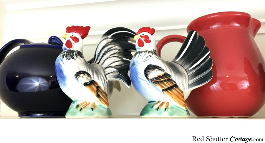 A vintage-looking pair of roosters are part of 3 Tips for Styling a Kitchen Hutch and Plate Shelf. www.redshuttercottage.com